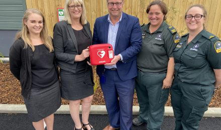 ASB representatives Charlotte Shaw and Heather McGowan, ŌCHT tenancy relations manager James Hadlee, and St John representatives Michelle Brett and Alice Earnshaw-Morris, at the official handover of the new AED at Reg Stillwell Place.