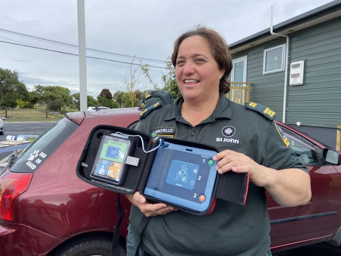 St John clinical advisor - Hauora Māori Michelle Brett with one of two AEDs installed at Reg Stillwell Place and Bridgewater Courts, New Brighton.
